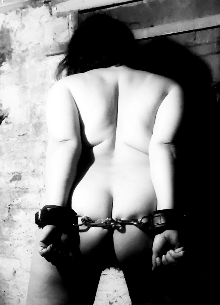 B&W nude, rear view, hands cuffed behind me.