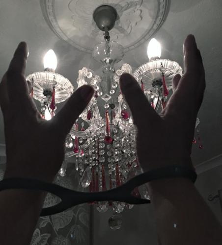 Cuffed hands held up in front of a red and clear glass chandelier