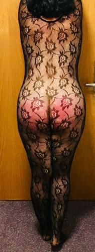 Hotel room door, black bodystocking, glowing red post-spanking butt